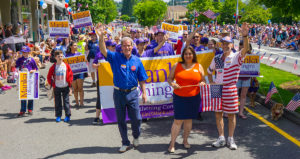 Manka Dhingra marches with Roger Goodman, Larry Springer, and a crowd of supporters in Kirkland.